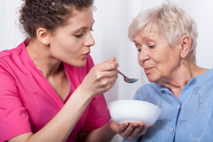 Nurse feeding an older lady