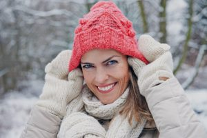 Frau im Winter setzt Mütze auf